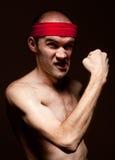 Grappige nerd die zijn bicepsen toont stock foto