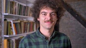 Grappige nerdy mens met krullend haar en snor die zich in bibliotheek bevinden en camera bekijken, vrolijk en positief stock video