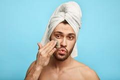 Grappige ontzagwekkende mens met een handdoek op zijn hoofd die een masker op zijn gezicht zetten royalty-vrije stock foto