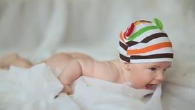 Grappige oude baby die van vier maanden bij zijn maag en het glimlachen liggen stock video