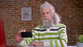 Grappige oude Kaukasische mens met ontzagwekkend wit lang haar en baard in het duren selfies terwijl het zitten bij de Desktop in stock videobeelden