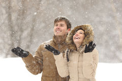 Grappige paar het letten op sneeuw in de winter stock afbeelding