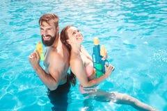 Grappige paartribunes in zwembad Zij stellen en glimlachen Het meisje kijkt omhoog Zij houden waterkanonnen in handen Zij zijn kl stock afbeelding