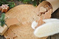 Grappige peperkoekmens op witte gebreide vuisthandschoenen op een mooie houten achtergrond Kerstboom met lichten wordt verfraaid  stock afbeeldingen
