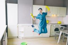 Grappige schonere sprongen omhoog in keuken Whe houdt omhoog haar handen Het meisje heeft rust die zij heeft opgehouden schoonmak stock afbeeldingen