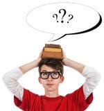 Grappige schooljongenfoto met boeken op het hoofd en vraagtekens in Toespraakballon Stock Foto