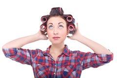 Grappige schoonheidsvrouw die met haarrollen omhoog kijken Royalty-vrije Stock Foto's