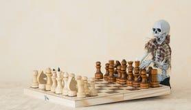 Grappige skeletzitting achter het de lijst en het spelen schaak Royalty-vrije Stock Foto's