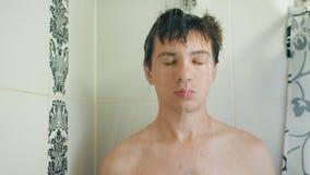 Grappige slaapmens die een douche nemen stock videobeelden