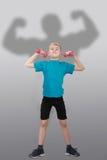 Grappige slanke jongen met het silhouet van de bodybuilder achter hem Royalty-vrije Stock Foto