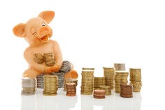 Grappige spaarvarken en stapels van muntstukken Stock Foto's