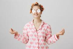 Grappige speelse charmante jonge vrouw met haar-krulspelden en katoenen stootkussens op ogen, die happilly terwijl binnen status  stock foto's