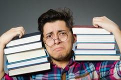 Grappige student met vele boeken Royalty-vrije Stock Afbeeldingen