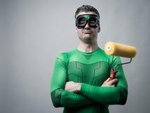 Grappige superhero met het schilderen van rol Stock Afbeeldingen