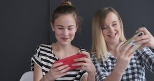 Grappige tieners die spel op mobiele telefoons spelen stock videobeelden