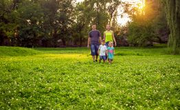 Grappige tijd - Mooie gelukkige kinderen die met ouders in park lopen royalty-vrije stock foto