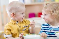Grappige twee glimlachend zeer positieve jonge geitjes die in kleuterschool eten royalty-vrije stock afbeelding