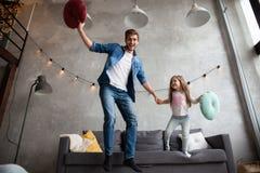 Grappige vader en het leuke jong geitjedochter lachen die hebbend pret in woonkamer, actieve familie die beweegt het spelen genie royalty-vrije stock foto's
