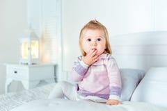 Grappige verbaasde blonde meisjezitting op bed in slaapkamer Stock Foto's