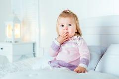 Grappige verraste blonde meisjezitting op bed in slaapkamer royalty-vrije stock fotografie