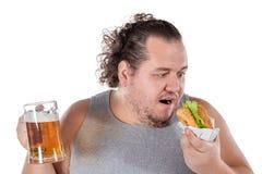 Grappige vette mens die hamburger eten en alcoholdrank op witte achtergrond drinken stock afbeeldingen