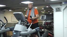 Grappige vette mens die oefeningen op de ellipsoïde in gymnastiek met hamburger doen stock video