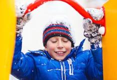 Grappige vrolijke jongen in jasje en hoeden het spelen in openlucht in de winter Royalty-vrije Stock Fotografie