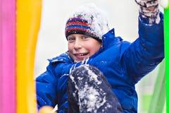 Grappige vrolijke jongen in jasje en hoeden het spelen in openlucht in de winter Royalty-vrije Stock Afbeelding