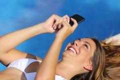 Grappige vrouw die haar slimme telefoon in de zomervakanties met behulp van Stock Foto's