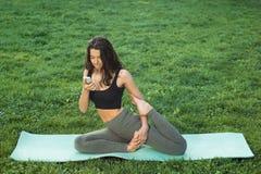 Grappige vrouw het leren yoga met smartphone stock foto's