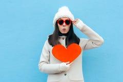 Grappige Vrouw in Liefde die een Hart op Blauwe Achtergrond houden royalty-vrije stock foto