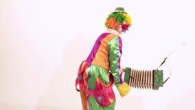 Grappige vrouwelijke clown die op een komische manier tegen witte achtergrond dansen stock footage