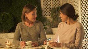Grappige vrouwelijke vrienden die het recentste roddels, drinken van koffie en lachen bespreken stock footage