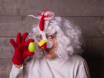 Grappige vrouwen in het vreemde kippenkostuum vragen - die eerste Kip of Ei kwam stock foto's