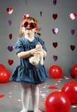 grappige witte Kaukasische meisjepeuter in studio met rode ballonsharten op grijze achtergrond die grappige glazen dragen Royalty-vrije Stock Foto's