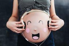 Grappige zwangere buik Zwangere vrouw stock foto