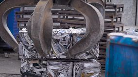 Grapple for scrap of stationary reloader is setting compressed scrap metal in the briquettes on a pallet outdoor in a stock video footage