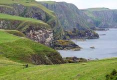 Gras überstieg Klippen, Wanderer mit Hund, Schottland Lizenzfreies Stockbild