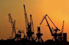 Grúas del puerto en la puesta del sol Fotografía de archivo