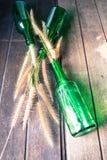 Gras in groene glasflessen op de houten achtergrond Stock Foto