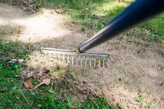 Gras harken, um für das Pflanzen von Samen vorzubereiten Lizenzfreie Stockfotos