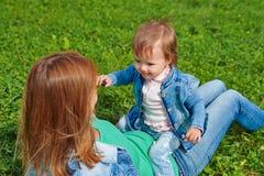 Gras-Hintergrundsommer der jungen Muttertochter Entspannungssitzender Lizenzfreie Stockfotografie