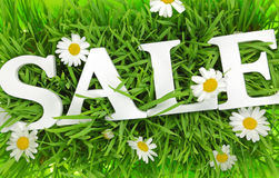 Gras mit Blumen und weißem Text Verkauf Stockfotos