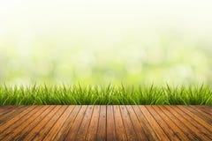 Gras mit Grün unscharfem Hintergrund und Holzfußboden Lizenzfreies Stockfoto