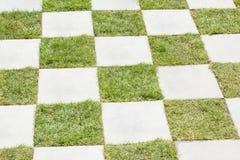 Gras zwischen Steinen, Blockpflasterung Stockfotos