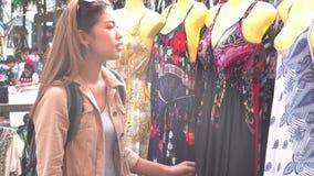Grasenkleidung der jungen Frau im Markt stock video