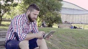 Grasentablette des jungen Mannes, sitzend auf Treppe Schieberschuß stock footage
