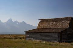 Grasgebied met schuur en van Grand Teton Bergen op achtergrond royalty-vrije stock afbeeldingen