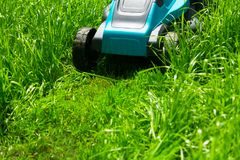 Grasmaaimachine die groen gras snijden stock afbeeldingen