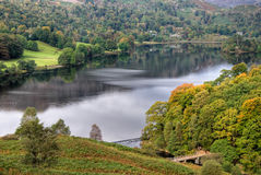 Grasmere in early Autumn. A view of Grasmere in the English Lake District, with early Autumn colours in the foreground trees which are lit by the sun. Two people Stock Image